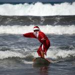Балиде серфингпен айналысып жүрген Санта-Клаус.