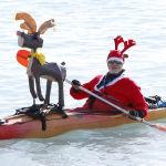 Санта-Клаус киімін киген ер адам қайықпен жүзіп барады.
