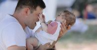 Мужчина держит на руках ребенка