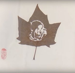 Китаянка вырезает картины на листьях