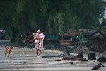 Женщина спасает собаку во время приближающегося шторма Пабук в Таиланде