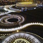 Стадион Краснодар с вечерней подсветкой и деревья парка, украшенные новогодними гирляндами