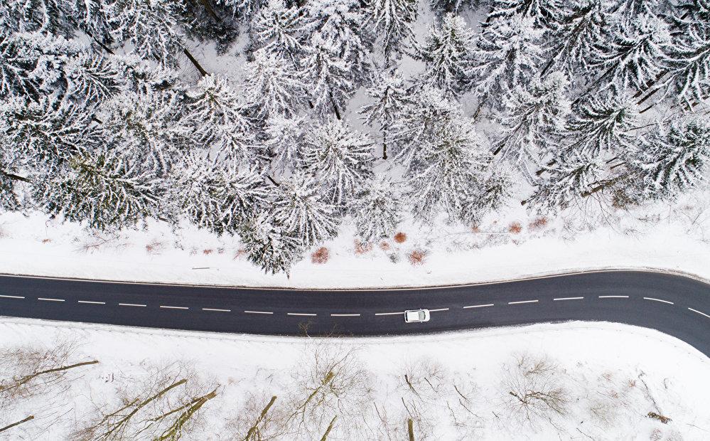 Аэросъемка дороги в зимнем лесу Рудных гор на востоке Германии