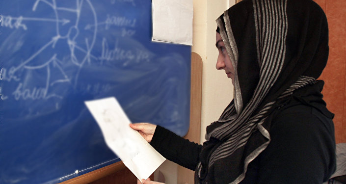 Архивное фото ученицы в хиджабе во время урока