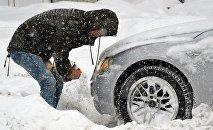 Мужчина очищает занесенную снегом машину