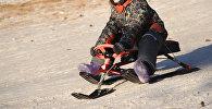 Ребенок катается с горки на снегокате