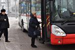 Женщина заходит в автобус