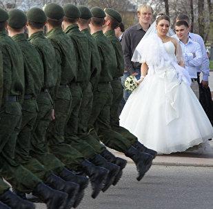 Архивное фото солдат, марширующих по набережной мимо молодоженов