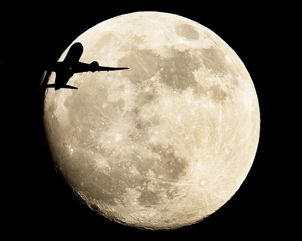 Самолет пролетает на фоне луны в Германии