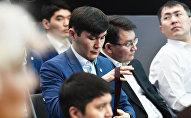Участники снимают галстуки во время церемонии открытия Года молодежи Тәуелсіздіктің ұрпақтары