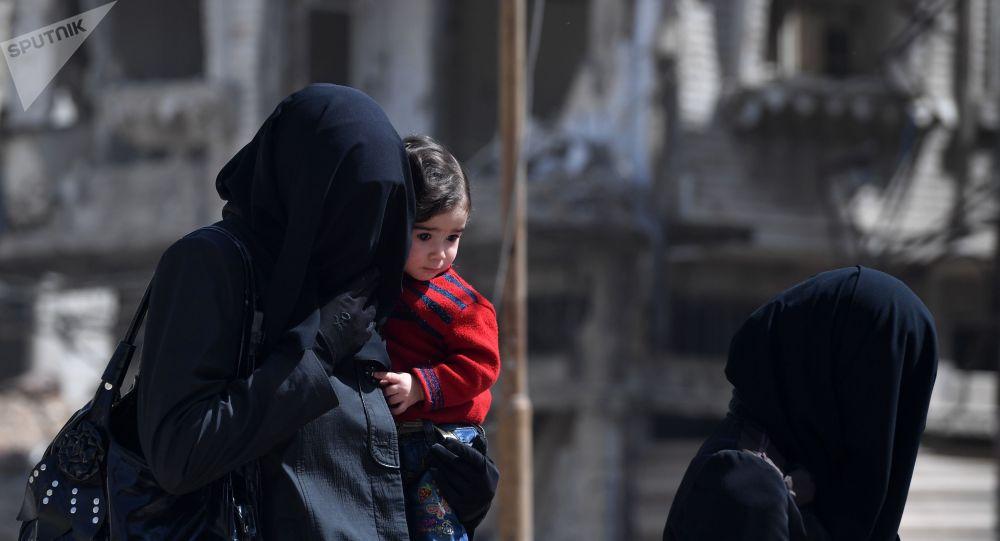 Женщина в хиджабе с ребенком на руках