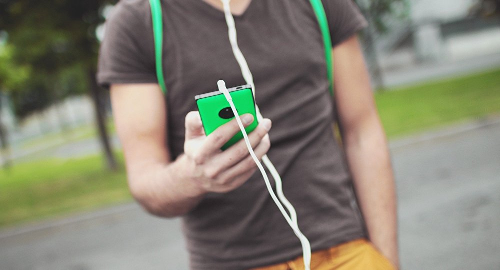 Мужчина слушает музыку на мобильном телефоне, иллюстративное фото