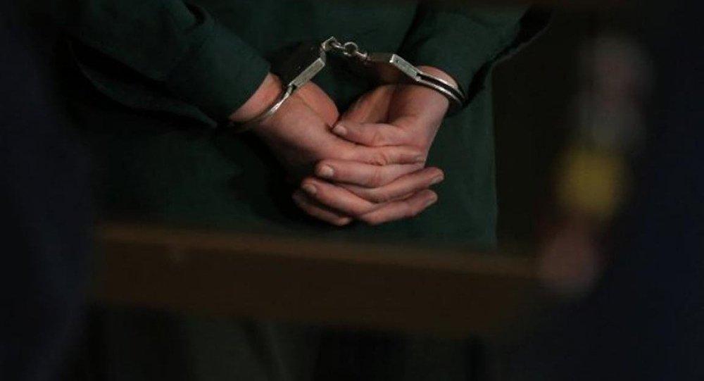 Архивное фото задержанного в наручниках