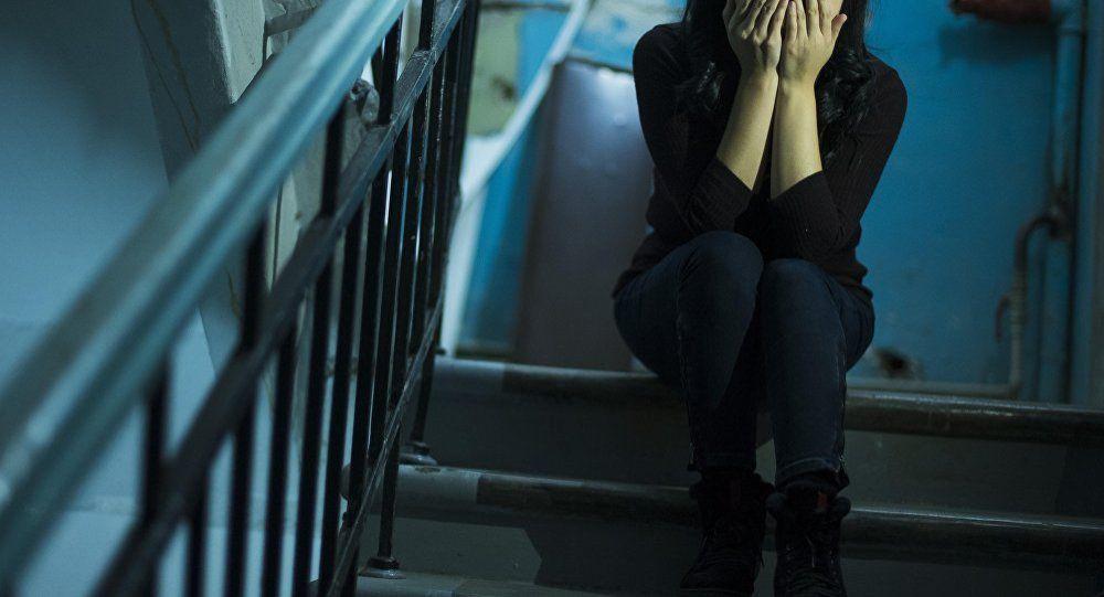 Девушка закрывает лицо руками, архивное фото