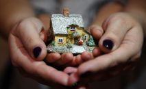 Женщина с ребенком держат макет дома