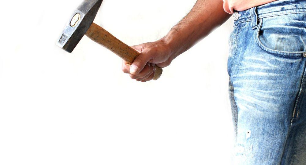 Мужчина с молотком в руке, иллюстративное фото