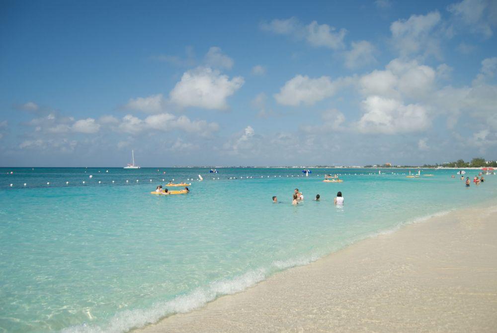 Отдыхающие на пляже Seven Mile Beach на Каймановых островах