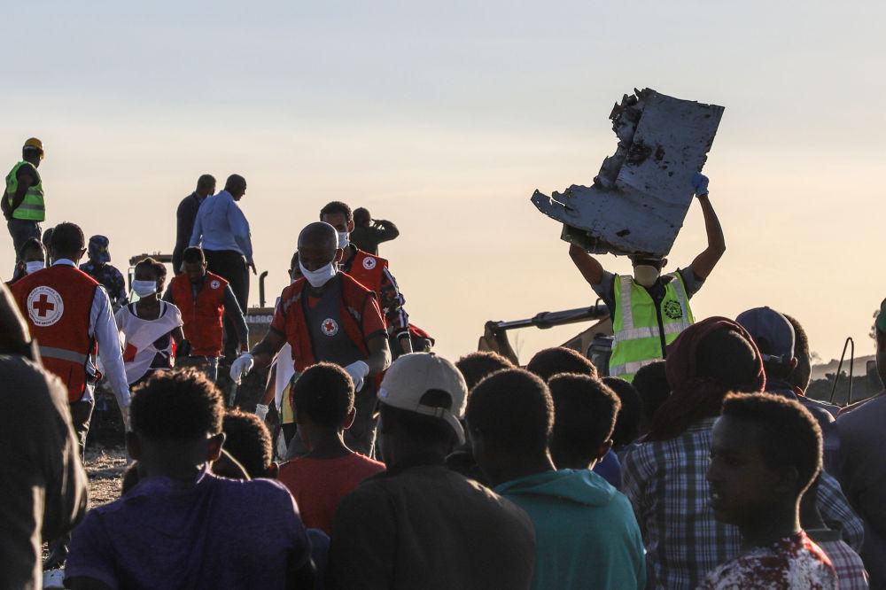 Люди с обломками самолета на месте авиакатастрофы Ethiopian Airlines