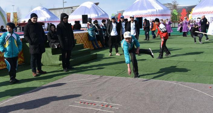 Дети играют в асыки в юрточном городке во время празднования Наурыз