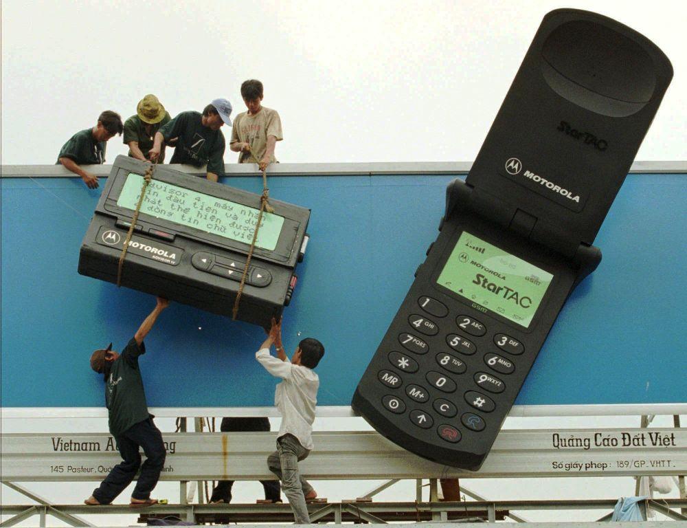 Рабочие размещают гигантские макеты пейджера и мобильного телефона с рекламой телекоммуникационных продуктов Motorola в городе Хошимин, 1996