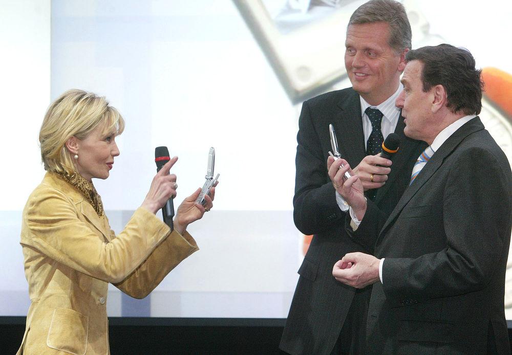 Немецкая журналистка и писательница Дорис Шредер-Кепф фотографирует своего мужа канцлера Герхарда Шредера мобильным телефоном со встроенной камерой, 2003 год.