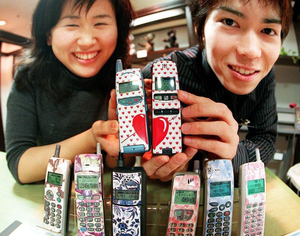 Молодая японская пара демонстрирует свои мобильные телефоны с дизайнерскими клеймами в универмаге Токи, 1999 год.