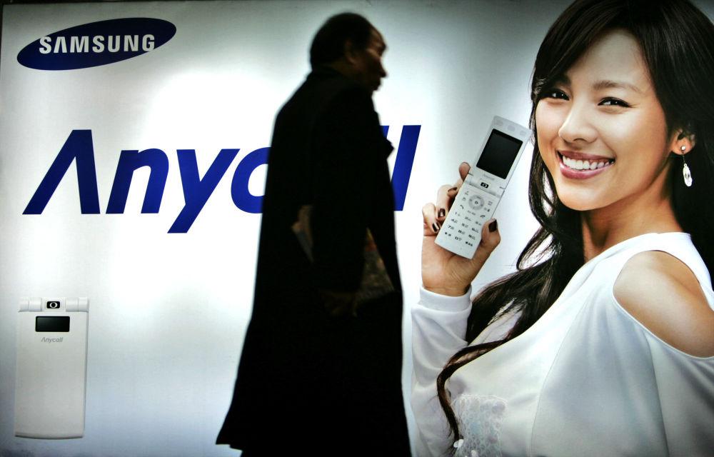 Пешеход идет мимо рекламного щита Samsung Mobile в Сеуле, Южная Корея. 2007 год