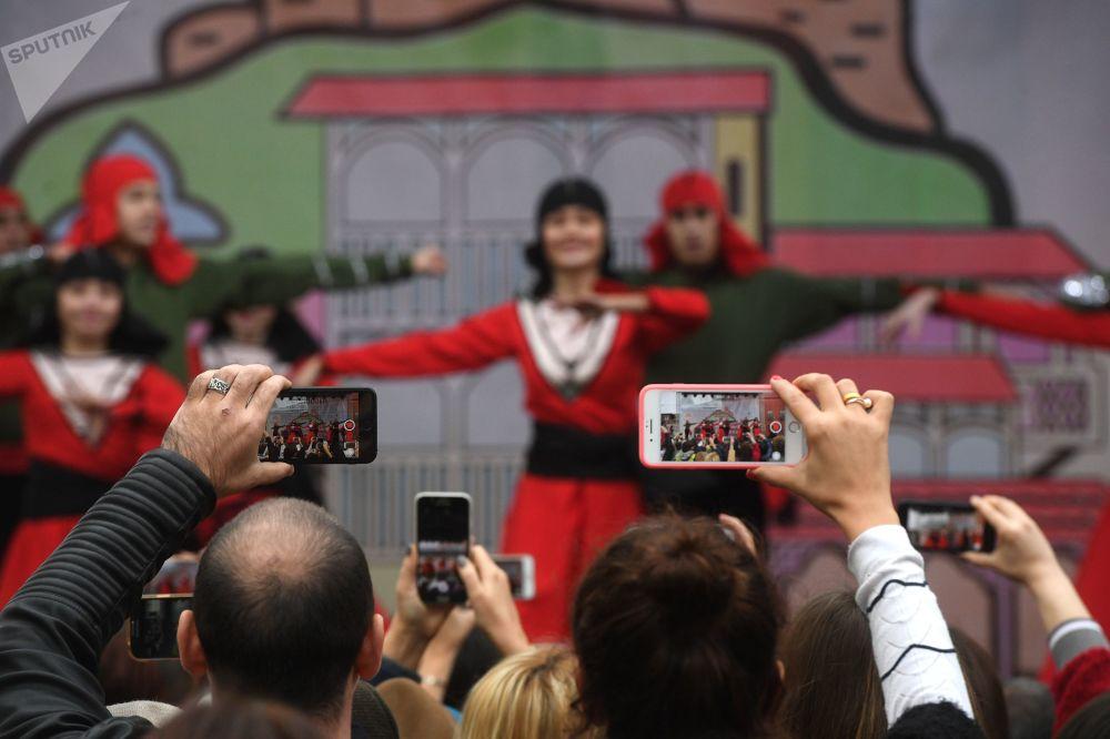 Зрители снимают на мобильные телефоны выступление танцевального ансамбля, 2018 год
