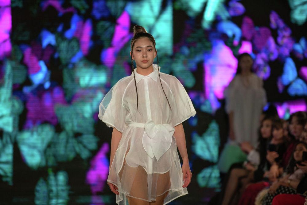 Юная модель показа KFW в воздушном коротком платье от казахстанского дизайнера Аиды Кауменовой