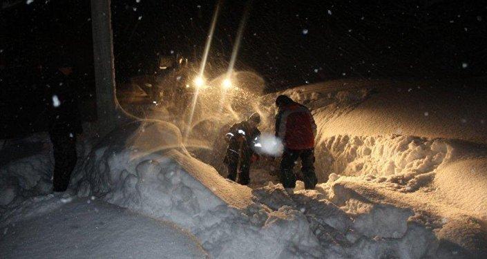 Спасатели вытаскивают машину из снега