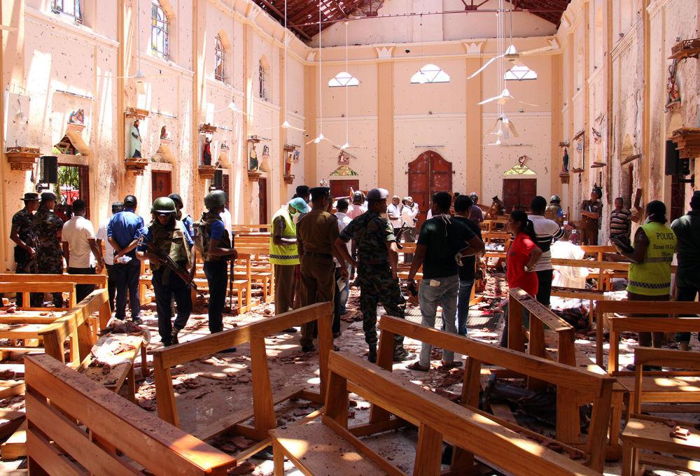 Сотрудники Службы безопасности Шри-Ланки проходят через обломки после взрыва в церкви Святого Себастьяна в Негомбо, к северу от столицы Коломбо (21 апреля 2019). Шри-Ланка