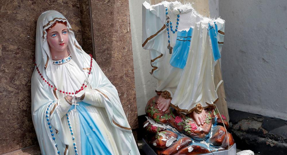 Разбитая после взрыва статуя Девы Марии перед святыней Святого Антония церкви Коччикаде в Коломбо (21 апреля 2019). Шри-Ланка
