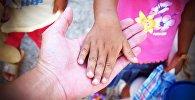 Ребенок протягивает руку взрослому