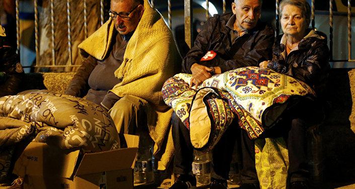 Мужчина укрывается одеялом, готовясь провести ночь под открытым небом после землетрясения в Аматриче (Италия)
