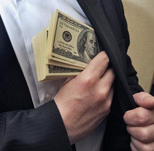 Архивное фото человека, прячущего в карман доллары