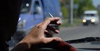 Водитель курит за рулем автомобиля, архивное фото