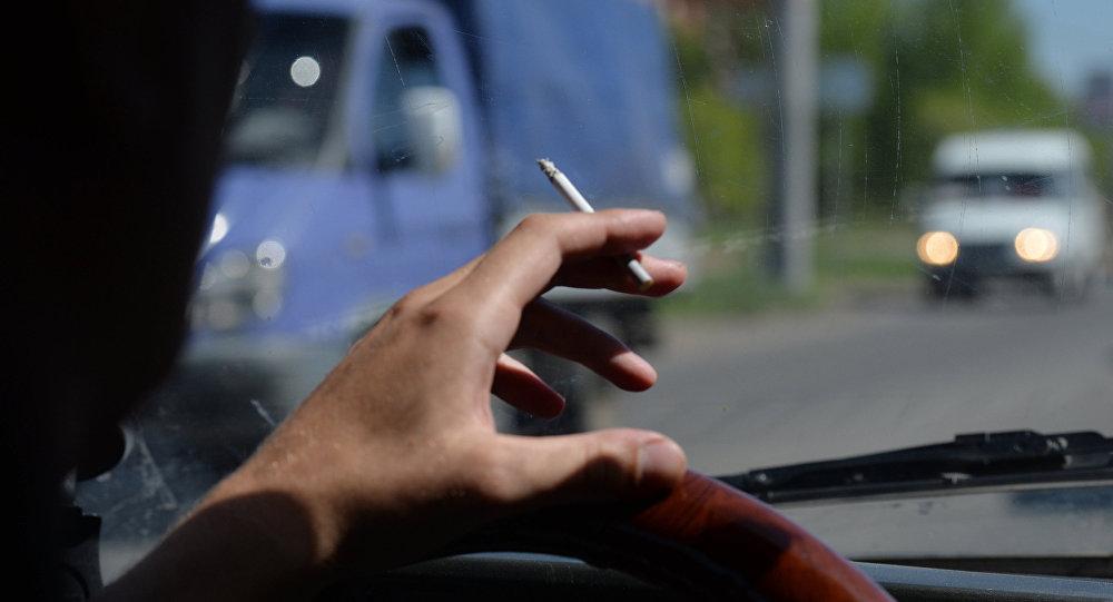 Водитель курит за рулем, архивное фото