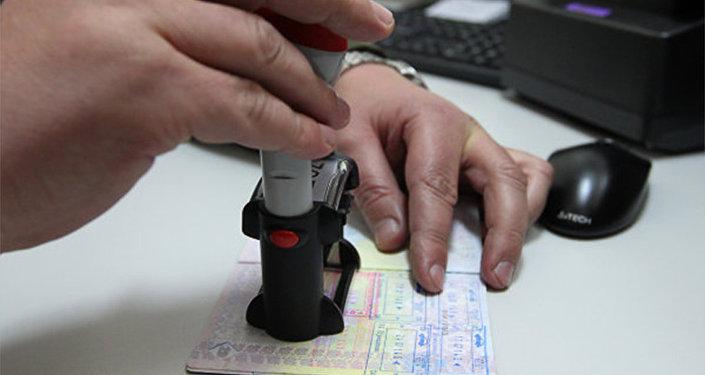 Архивное фото сотрудника погранслужбы, ставящего штамп о пересечении границы